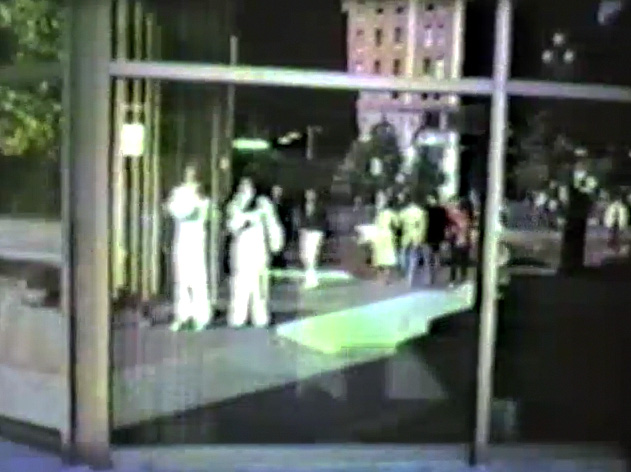 Reflection in downtown wind of two men in hazmat suits.