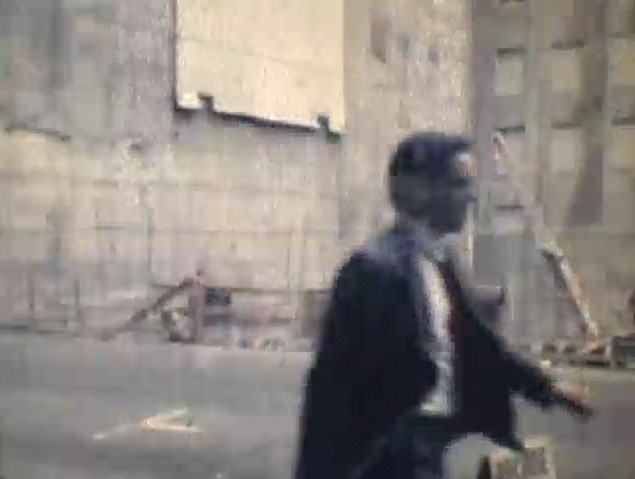 Man walking past construction site wearing a suit